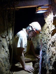 """Dans la mine Patris, Patrick Clerc (Archéologue de l'INRAP) nous dévoile le """"puit"""" que lui et des bénévoles ont dégagé pour atteindre un vieux plancher datant potentiellement du XIIème siècle."""