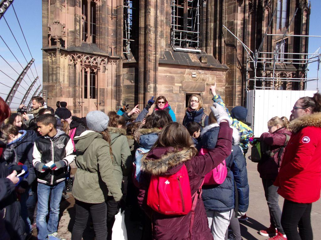 Julie lanson devant un groupe d'élèves sur le toit de la cathédrale de Strasbourg ©E.Schildknecht/Ariena